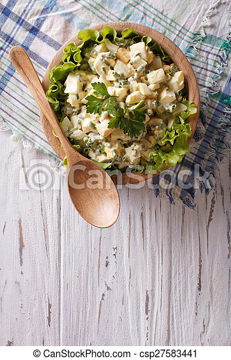 egg salad in a wooden bowl, vertical view from above