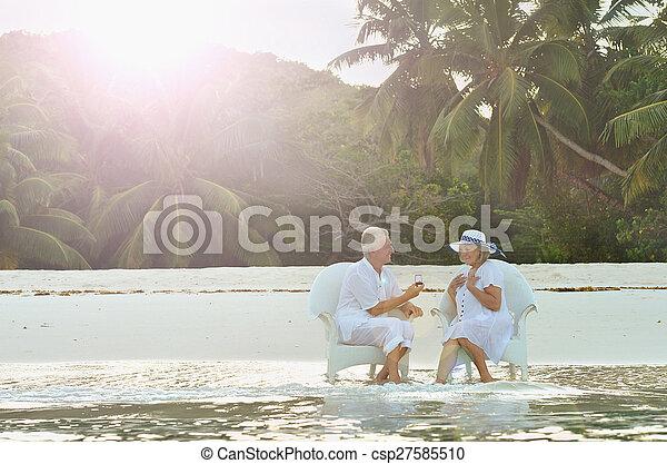 Elderly couple sitting on a beach