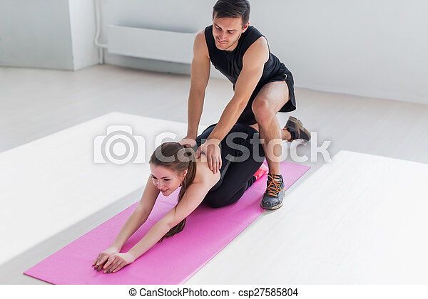 woman sitting doind exercise for flexible back male trainer helping her concept sport health fitness aerobics gymnastic