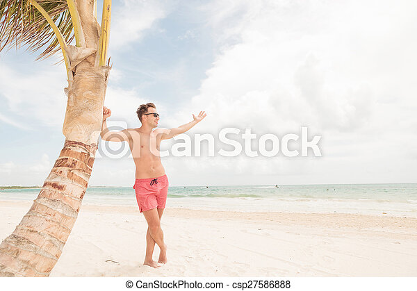 Smiling lifeguard leaning on a palm tree