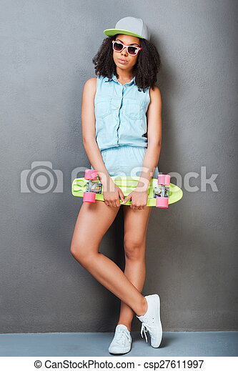 Carefree youth. Full length of attractive young African woman holding colorful skateboard and smiling while standing against grey background