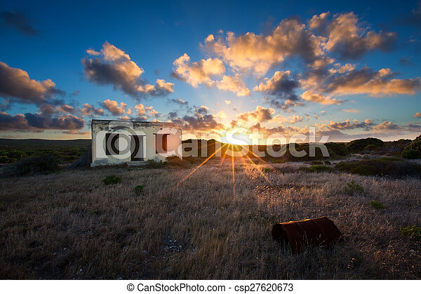 Old small deserted house in field with cloud sunset landscape - csp27620673