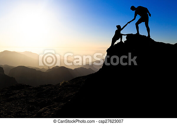 Teamwork couple hiking help each other trust assistance silhouette in mountains, sunset. Team of climbers man and woman hiker helping each other on top of mountain, climbing trust, beautiful sunset landscape.