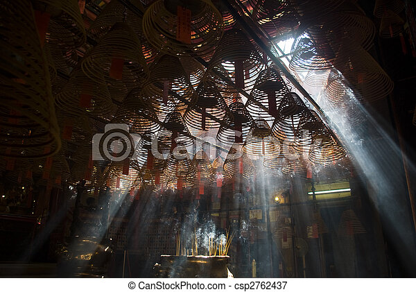 Incense and crepuscular rays in Hong Kong Man mo temple.        architecture attraction building cheong crepuscular god historic hollywood hong incense kong kwan light literature man miu old peach pray rays religion road sheung sightseeing smoke temple tourism tourists travel wan war - csp2762437