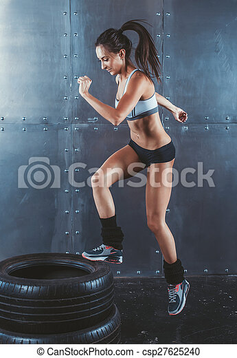 Sporty active fit woman box jumping. Female athlete is performing tire jumps fitness, sport, training and lifestyle concept.
