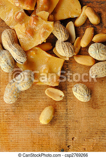 Peanut Brittle with Peanuts on Wood Table - csp2769266