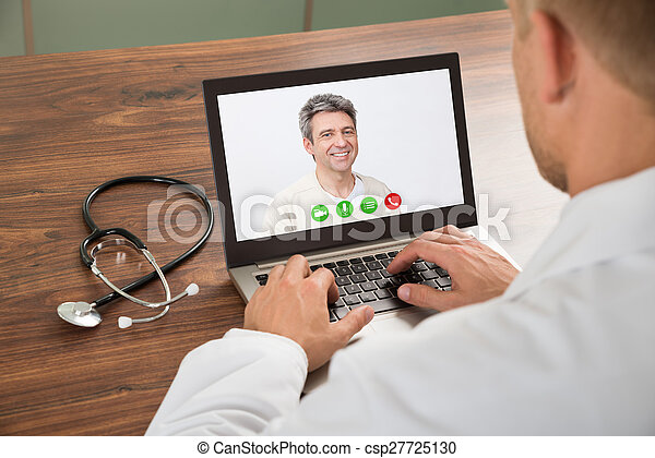 Close-up Of Doctor Talking To Male Patient Through Video Chat On Laptop At Desk
