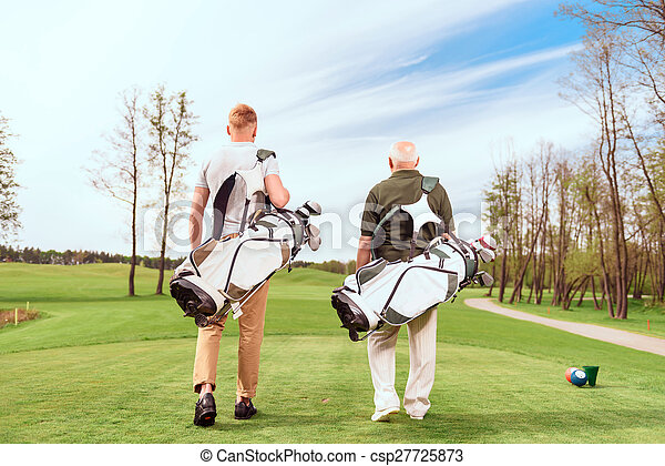 Back view of walking golf players on course