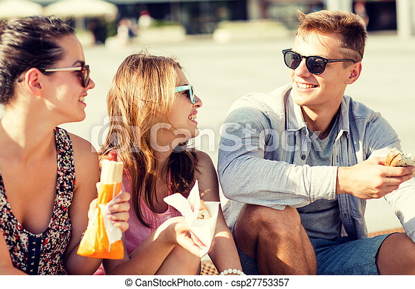 group of smiling friends sitting on city square
