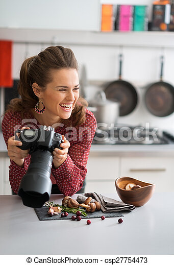 Smiling woman food photographer taking a break in kitchen