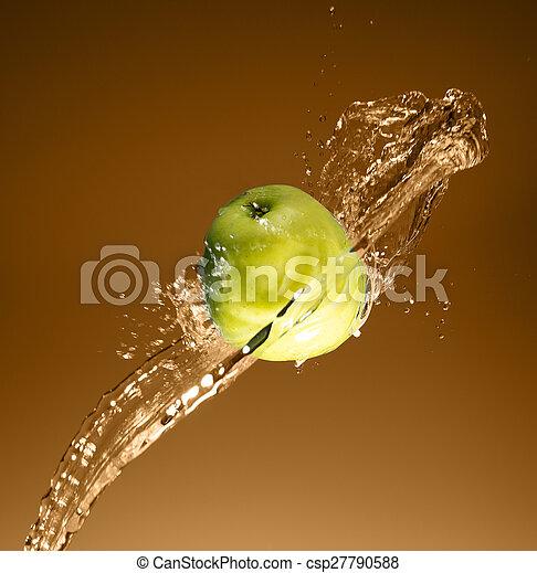 Green apple with water splash, on beige