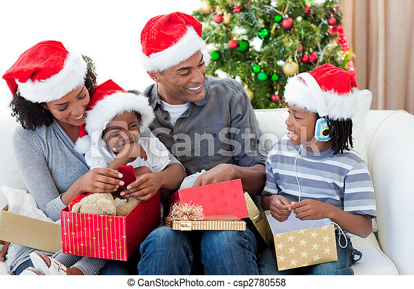 Happy Afro-American family opening Christmas presents - csp2780558