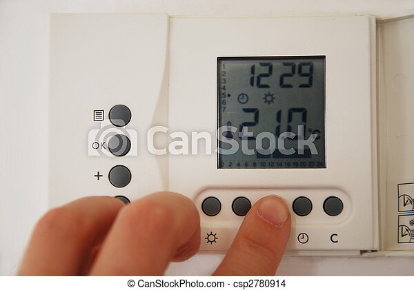 hand setting the temperature of the heating thermostat  - csp2780914