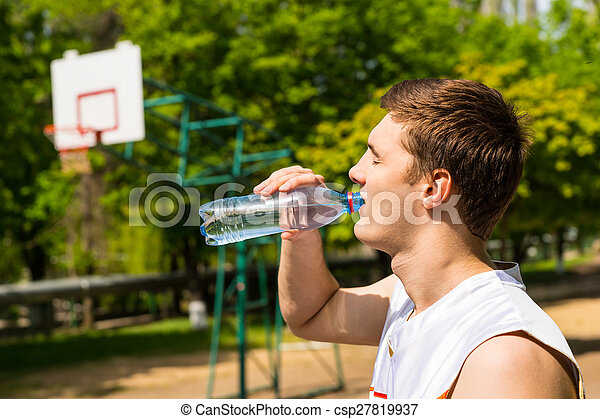 Man Drinking Water from Bottle on Basketball Court