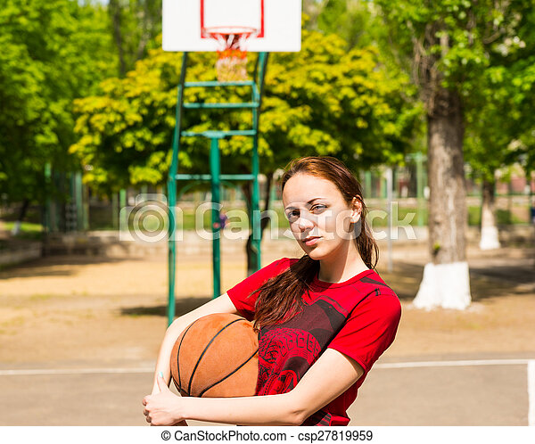 Woman Standing on Basketball Court Holding Ball