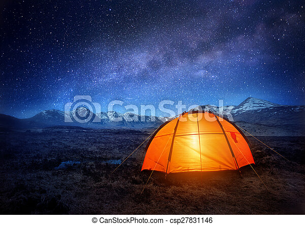 A camping tent glows under a night sky full of stars. Outdoor Camping adventure.