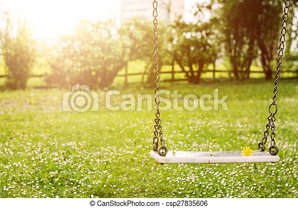 Abandoned swing in warm sunny light with flowers in the spring season