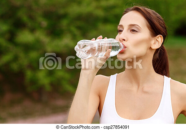 Pretty girl drinking water in park