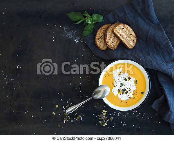 Pumpkin soup with cream, seeds, bread and fresh basil on grunge black background