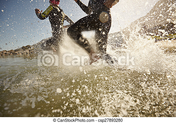 Two triathlon participants running into the water for swim portion of race. Splash of water and athletes running. Focus on water splash.