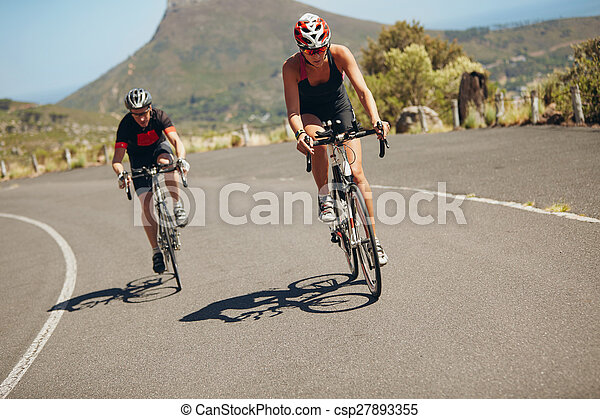 Cyclist riding bikes on open road