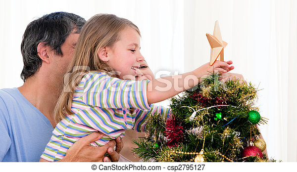 Smiling family decorating a Christmas tree in the living-room - csp2795127