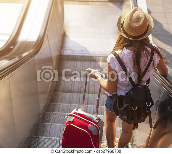 girl with suitcase down escalator