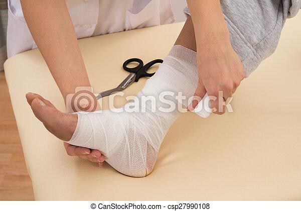 Nurse Tying Bandage On Patient\'s Foot