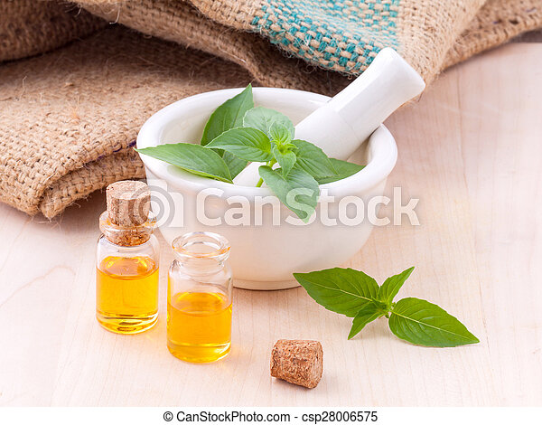 Alternative medicine lemon basil oil natural spas ingredients for aroma aromatherapy with mortar on wooden background.