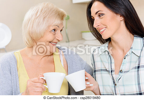 Grandmother and granddaughter drinking tea