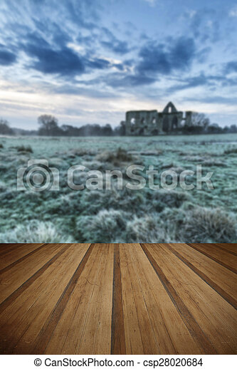 Beautiful sunrise landscape of Priory ruins in countryside location with wooden planks floor