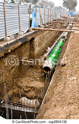 Metal pipes with thick heat isolation lieing in the trench. - csp2804136
