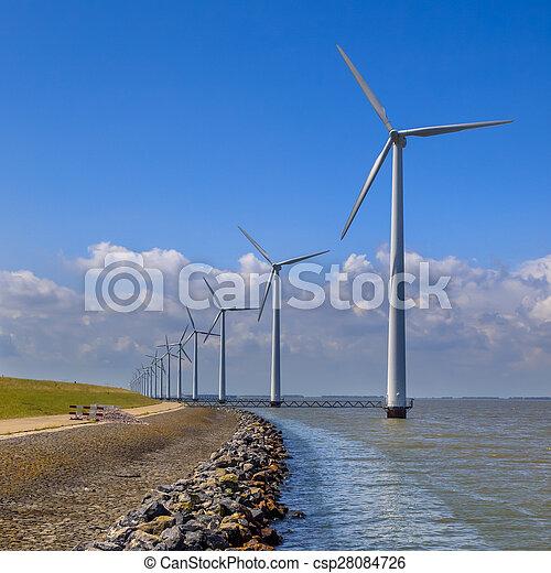 Row of wind turbines along a breakwater - csp28084726