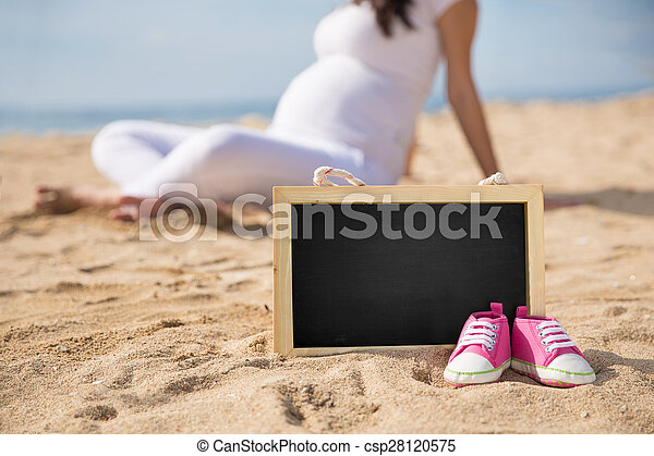 Pink Toddler sneakers and mini chalk board on the sand with pregnant woman on the background