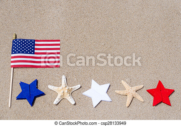 Amrican flag with white, blue and red stars and starfishes on the sandy beach - USA holidays concept