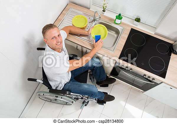 Man On Wheelchair With Sponge Washing Dishes