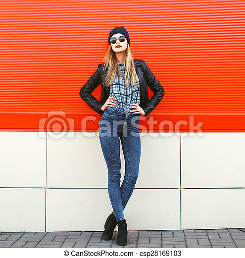 Street fashion concept - stylish hipster woman in rock black style posing against a colorful urban wall