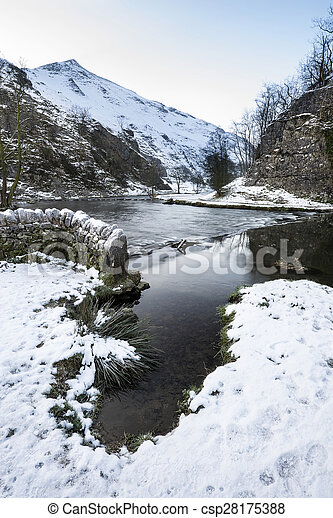 River flowing through snow covered Winter landscape in forest valley - csp28175388