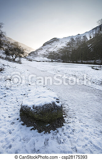 River flowing through snow covered Winter landscape in forest valley - csp28175393