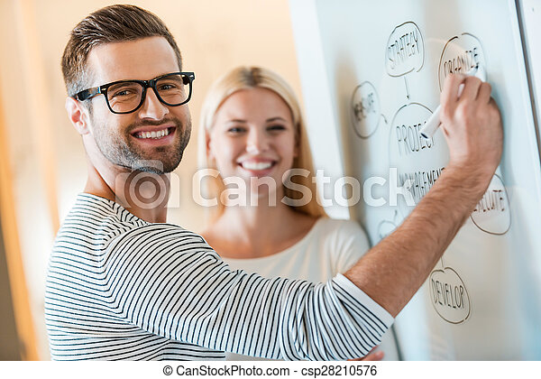 Planning business together. Confident young man and woman looking at camera and smiling while both standing near whiteboard in office