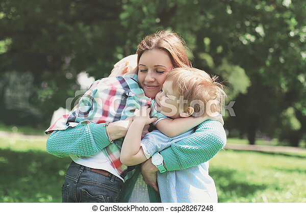 Family happiness! Happy mother tenderly embracing his two sons in spring day, warm feelings of the mother, moment of life, happy family on nature
