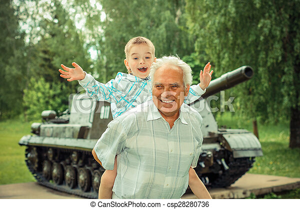 Grandfather and grandson are photographed on a background of vintage tank - csp28280736