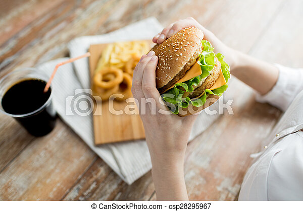 close up of woman hands holding hamburger