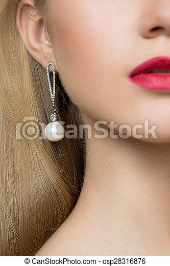 girl ear in jewelry earrings close up