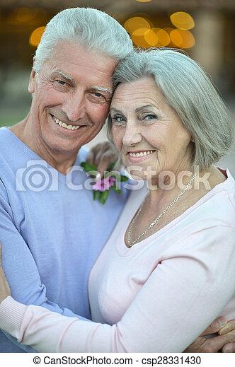 Elderly couple standing outdoors