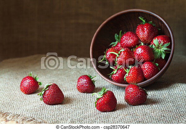 Strawberry natural healthy nutrition organic food in rustic clay dish on vintage kitchen background. Vegetarian, full of vitamin dessert.