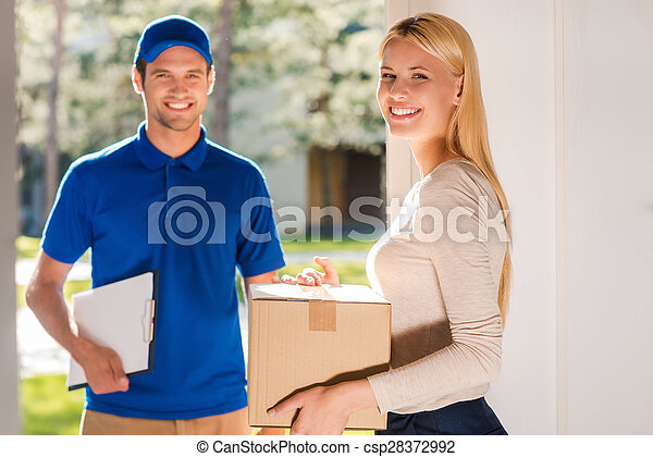 First class delivery service. Beautiful young woman holding a cardboard box while young delivery manholding clipboard and smiling