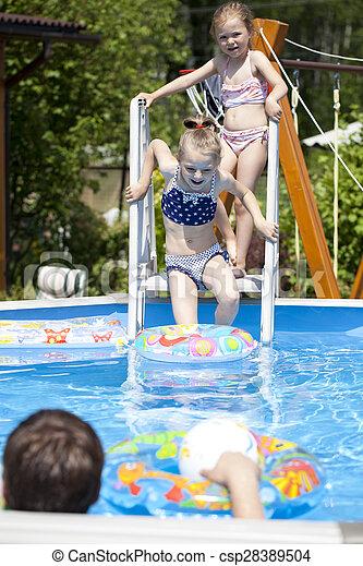 Two sisters in bikini near swimming pool. Hot Summer