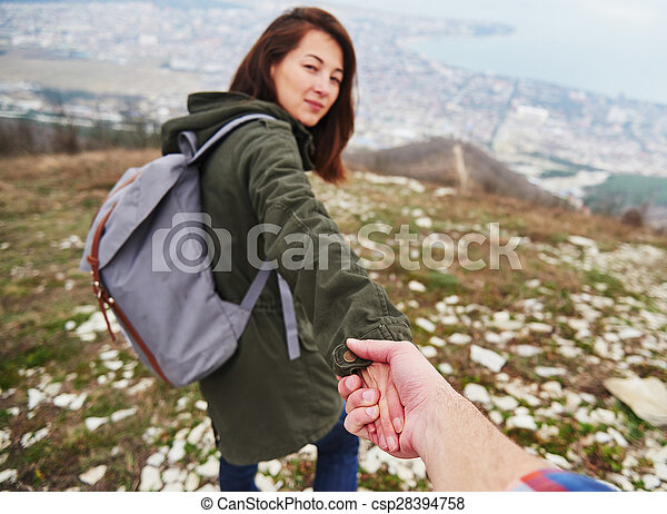 Woman holding man\'s hand and leading him outdoor