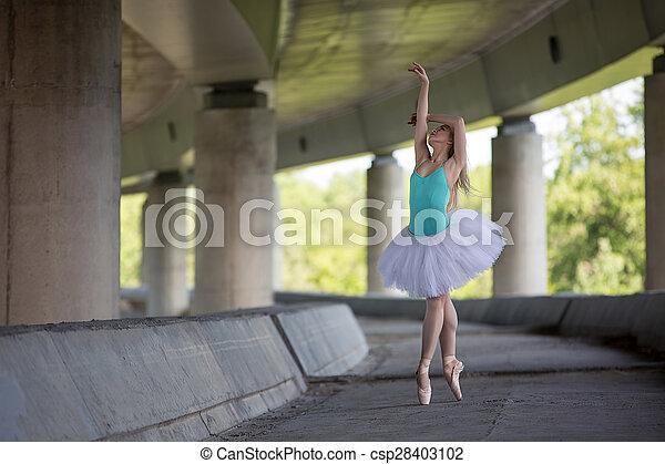 Graceful ballerina doing dance exercises on a concrete bridge